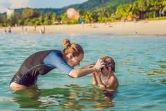 El instructor de la natación de la mujer para los niños está enseñando a un muchacho feliz a nadar en el mar foto de archivo