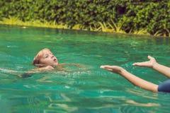 El instructor de la natación de la mujer para los niños está enseñando a un muchacho feliz a nadar en la piscina foto de archivo libre de regalías