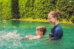 El instructor de la natación de la mujer para los niños está enseñando a un muchacho feliz a nadar en la piscina imágenes de archivo libres de regalías