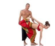 El instructor de la yoga ayuda a la muchacha a realizar asana Foto de archivo