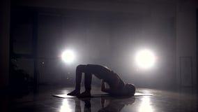 El instructor de la yoga muestra ejercicio flexible en un gimnasio almacen de video