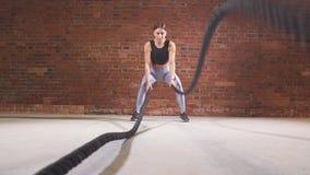 El instructor de sexo femenino del crossfit prueba que las cuerdas de entrenamiento son un entrenamiento muy dinámico Cámara lent almacen de video