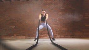 El instructor de sexo femenino del crossfit prueba que las cuerdas de entrenamiento son un entrenamiento muy dinámico Cámara lent almacen de metraje de vídeo