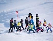 El instructor del esquí en un traje de pingüino estudia a niños en escuela del esquí Estación de esquí en las montañas, Austria,  Fotografía de archivo