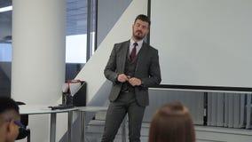 El instructor del negocio conduce el entrenamiento para los profesionales en compañía grande almacen de video