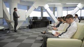 El instructor del negocio escribe y habla con los empleados en compañía almacen de metraje de vídeo