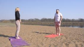 El instructor dinámico de la yoga de la mujer caucásica bonita enseña a un hombre lleno con una barba, clases de la yoga en la na almacen de video