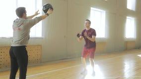 El instructor en sudadera con capucha gris entrena a su sala joven en burpee del gimnasio y coge la bola almacen de video