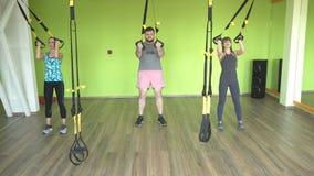 El instructor enseña en el gimnasio para practicar a un hombre en las bisagras del rato que realiza un empuje facial del ejercici almacen de metraje de vídeo