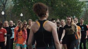 El instructor femenino aerobio que marcha en el lugar con la gente aprieta en parque de la ciudad metrajes