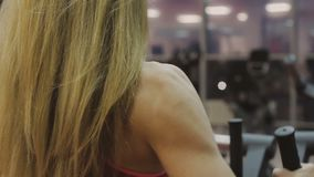 El instructor femenino muy hermoso entrena en una máquina de la aptitud en un club de fitness almacen de metraje de vídeo
