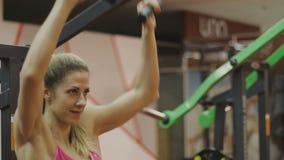 El instructor femenino muy hermoso entrena en una máquina de la aptitud en un club de fitness almacen de video