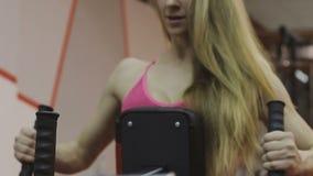 El instructor femenino muy hermoso entrena en una máquina de la aptitud en un club de fitness metrajes