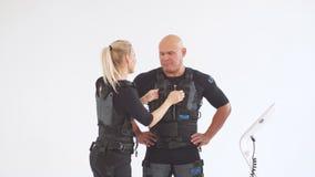 El instructor femenino rubio ayuda al hombre a atar el electrodo en el traje del ccsme almacen de video