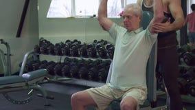 El instructor guarda sus manos en los codos del cliente mayor almacen de video