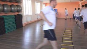 El instructor hermoso de la muchacha en una lección de grupo en un centro de aptitud moderno muestra a hombres caucásicos ejercic almacen de metraje de vídeo