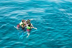 El instructor muestra a niños la belleza del mundo subacuático foto de archivo