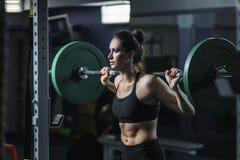 El instructor muscular atractivo potente de CrossFit de la mujer hace entrenamiento con el barbell foto de archivo libre de regalías