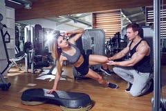 El instructor personal ayuda a la muchacha a hacer ejercicios en el gimnasio foto de archivo libre de regalías