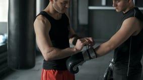 El instructor pone guantes de boxeo en atleta antes de entrenar cámara lenta 4k almacen de metraje de vídeo