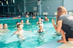 El instructor trabaja con los niños en piscina Imágenes de archivo libres de regalías