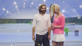 El instructor y el jugador habla en el campo de tenis metrajes