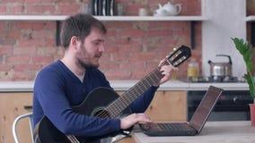 El instrumento musical atado juego de aprendizaje masculino del feliz guitarrista barbudo utiliza el ordenador portátil con la e metrajes