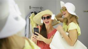 El intentar feliz de la mujer nuevos lentes de sol en el guardarropa en la tienda de ropa Amigos femeninos que tienen ropa de las almacen de video