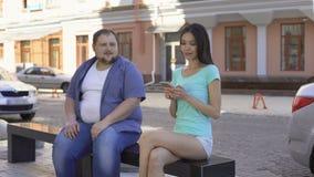 El intentar masculino gordo conseguir conocido con la hembra joven deportiva en banco almacen de video