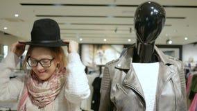 El intentar rubio atractivo en el sombrero negro en el centro comercial, opción de la ropa para mujer en la tienda, muchacha shop metrajes