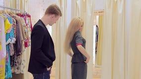 El intentar rubio hermoso sonriente en el traje con su novio en sitio apropiado almacen de metraje de vídeo
