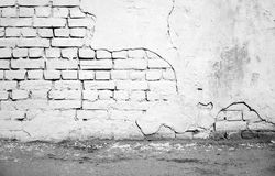 El interior, blanco dañó la pared de ladrillo y el asfalto Fotografía de archivo