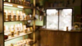 El interior de la cafetería del té empañó el fondo abstracto, estantes con las muestras, la luz trasera y el escaparate iluminado Foto de archivo