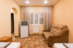 El interior de un pequeño cuarto con el sofá cama y dos solas camas, ventanas, TV y refrigeradores Foto de archivo libre de regalías