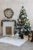 El interior del Año Nuevo con una chimenea, un piel-árbol y las velas imagen de archivo libre de regalías