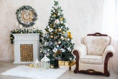 El interior del Año Nuevo con una chimenea, un piel-árbol y las velas Imágenes de archivo libres de regalías