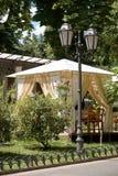 El interior del café de la calle en el parque verde de la ciudad, adornado con las flores, estación de verano, día soleado brilla Imagen de archivo libre de regalías