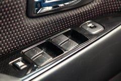 El interior del coche con vistas al tablero de instrumentos, a las ventanas y a los botones del espejo con gris claro y la franja fotografía de archivo libre de regalías