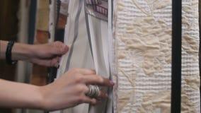 El interiorista en su estudio muestra muestras de la tela almacen de metraje de vídeo