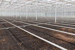 El invernadero vacío con el suelo se preparó para el cultivo de plantas Foto de archivo libre de regalías
