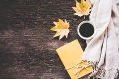 El invierno acogedor, taza de café caliente con la melcocha, calienta el suéter y el arce hechos punto en el viejo fondo de mader Imagen de archivo libre de regalías