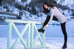 El invierno bonito del patinaje de hielo de la mujer al aire libre, lleva patines Montañas en el fondo Imagenes de archivo