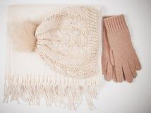 El invierno caliente hizo punto la ropa - sombrero, bufanda, guantes en un fondo blanco Imagen de archivo