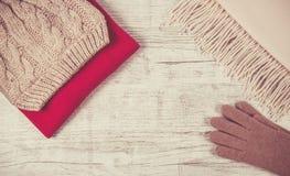 El invierno caliente hizo punto la ropa - sombrero, bufanda, guantes en un fondo de madera Fotos de archivo libres de regalías