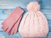 El invierno caliente hizo punto la ropa - sombrero, guantes en un fondo azul Foto de archivo libre de regalías