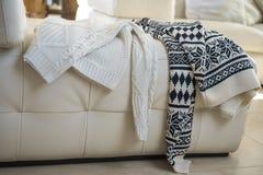 El invierno caliente hizo punto los suéteres dos personas caídas en el sofá después de igualar Concepto del día de tarjetas del d imagen de archivo