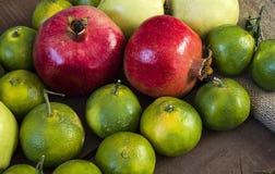 El invierno da fruto en el piso de madera, membrillo, granada, imágenes del mandarín Foto de archivo