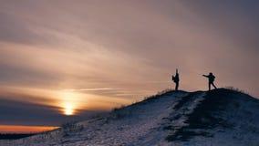 El invierno de la gente salta luz del sol de la nieve de la alegría de la fotografía de la silueta grupo de turistas que caminan  metrajes