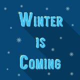 El invierno de la inscripción está viniendo con los copos de nieve y Foto de archivo libre de regalías