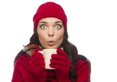El invierno de la mujer con los ojos abiertos de la raza mixta que lleva guantes sostiene la taza Fotografía de archivo libre de regalías